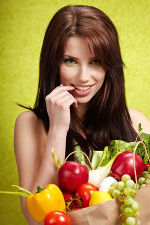 Portrait of a girl holding in hands full of different fruits and vegetables  photo