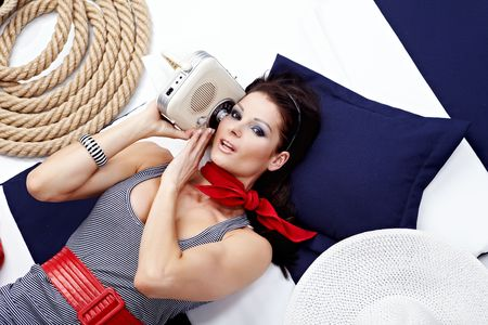 Pin-up woman laying and listening radio photo