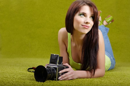 woman with camera on green spring background Stock Photo - 6929582