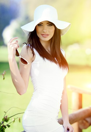 spring hat: Portrait of a beautiful young woman in summer park.