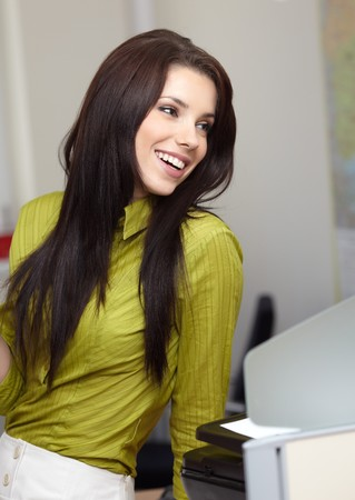 ordinary woman: Beautiful smiling business woman sitting and relaxing in the office  Stock Photo