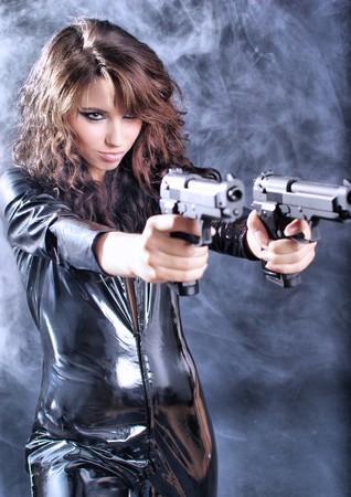 beautiful sexy girl holding gun . smoke background photo
