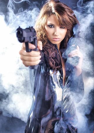 pistolas: pistola de explotaci�n de hermosas sexy girl. Fondo de humo  Foto de archivo