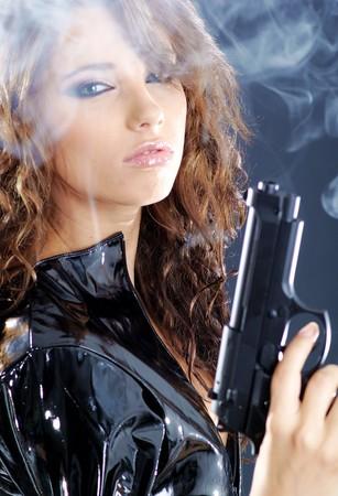 mujer con pistola: pistola de explotaci�n de hermosas sexy girl. Fondo de humo  Foto de archivo