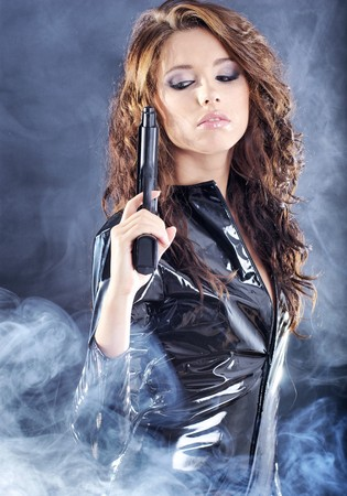 beautiful sexy girl holding gun . smoke background Stock Photo - 7017052