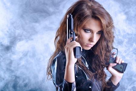 croft: beautiful sexy girl holding gun . smoke background