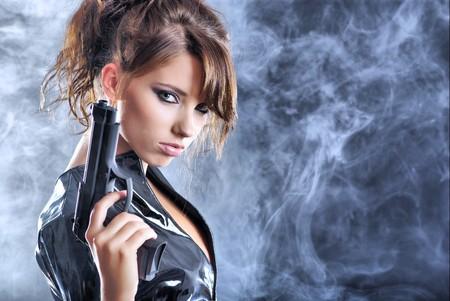 mortale: bella ragazza sexy azienda pistola. sfondo di fumo
