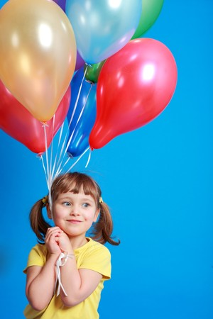 helium: little girl holding colorful balloons on a blue background