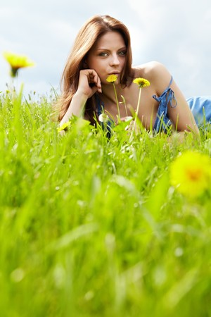 The image of a girl wearing blue dress  in the green field  photo
