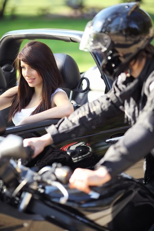 Sexy girl in car looking a man on a motorcycle photo