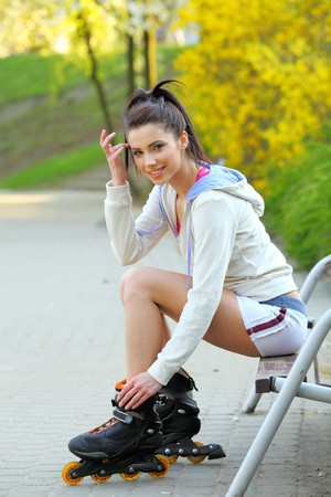 rollerblades: a young woman rides rollerblades in the park