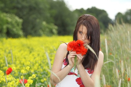 Young woman with long hair in poppies field photo