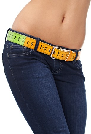 Closeup photo of a slim womans abdomen and jeans with measuring tape instead of a belt.  photo