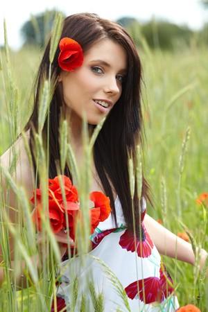Summer girl running in poppy field photo
