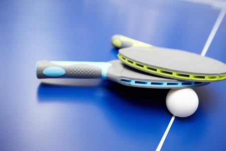Two table tennis  rackets and balls on a blue table with net photo