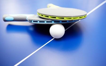 ping pong: Dos raquetas de tenis de mesa y bolas sobre una mesa azul con un neto de  Foto de archivo