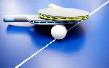 pong: Two table tennis rackets and balls on a blue table with net