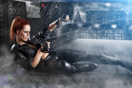 mooie sexy meisje bedrijf pistool. rook achtergrond  Stockfoto
