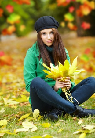Fashion woman in autumn park holding yellow leaf Stock Photo - 7762246