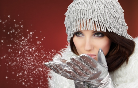 blow kiss: Attracive girl in santa cloth blowing snow from hands. Stock Photo