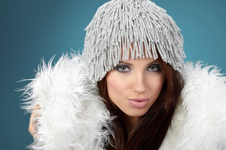 Portrait of beautiful brunette woman wearing sexy winter clothes on blue background photo