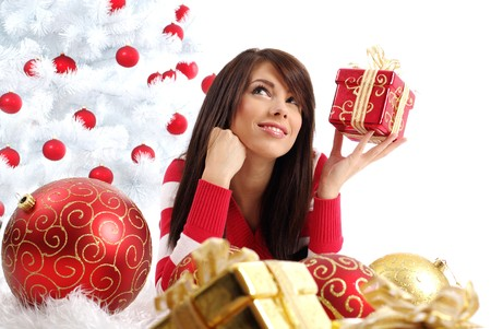 Beautiful girl with gift box next to white christmas tree photo