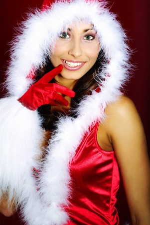 Portrait of beautiful brunette woman wearing sexy santa claus clothes on red background  photo