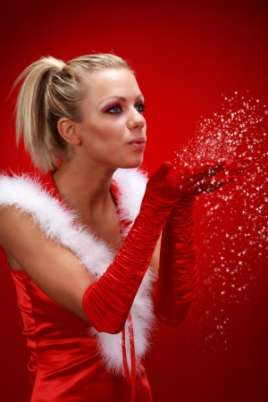 chica: Attracive sexy girl in santa cloth blowing snow from hands.