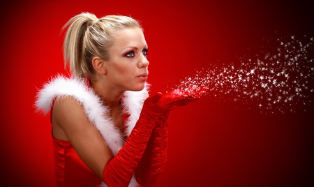 blow kiss: Attracive sexy girl in santa cloth blowing snow from hands.