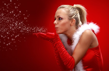 Attracive girl in santa cloth blowing snow from hands. Stock Photo