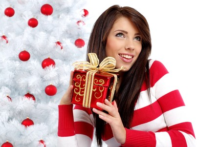 Beautiful woman with gift  next to white christmas tree photo
