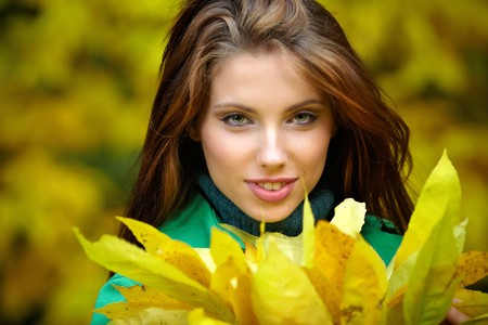 Fashion woman in autumn park holding yellow leaf  photo