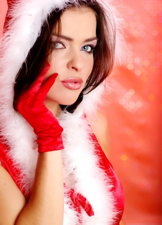Portrait of beautiful sexy girl wearing santa claus clothes on red background photo