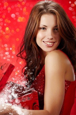 magic box: sexy girl smiles and holding a gift in magic packing  Stock Photo