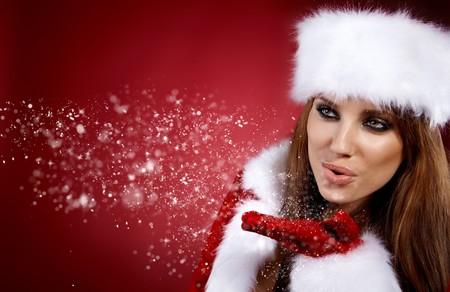 Foto de la niña de Navidad de moda soplando la nieve.  Foto de archivo