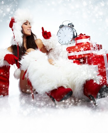Santa girl pointing at clock showing five minutes to midnight  photo