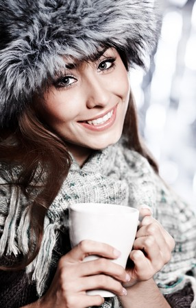 Girl blowing on hot drink dressed in winter clothing  Stock Photo - 8196092
