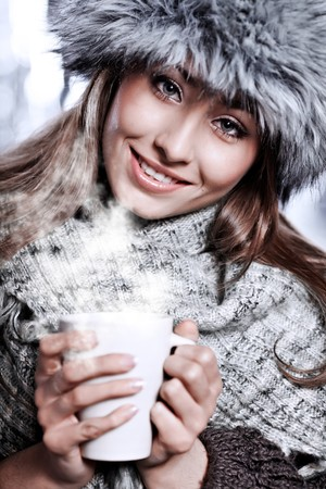 Girl blowing on hot drink dressed in winter clothing  photo
