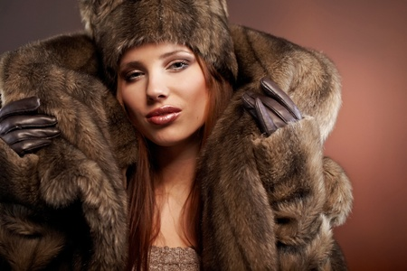 Attractive woman in brown  fur coat with hood  photo