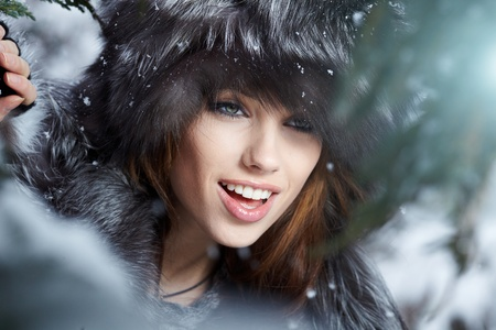 Beautiful young woman in winter forest  Reklamní fotografie