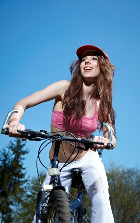 outdoor fitness: Young woman on a bicykle outdoors smiling  Stock Photo