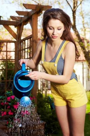 Cheerful girl watering flowers photo