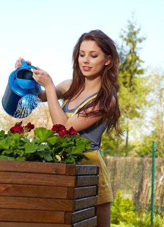 watering plants: Cheerful girl watering flowers