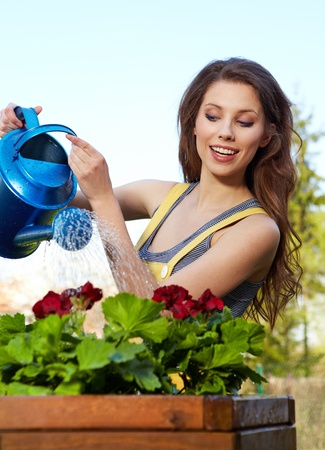 woman gardening: Cheerful girl watering flowers