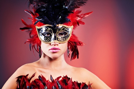 Beautiful young woman in carnival mask and feather boa.  photo