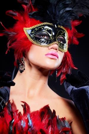 masked woman: Joven y bella mujer en m�scara de Carnaval y boa de plumas.