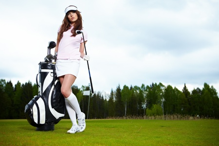 woman golf: Portrait of a woman holding a golf club in her hands on a green