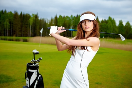 Portrait of a woman holding a golf club in her hands on a green Stock Photo - 9565192