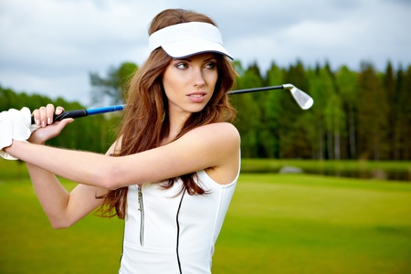 Portrait of a woman holding a golf club in her hands on a green  photo