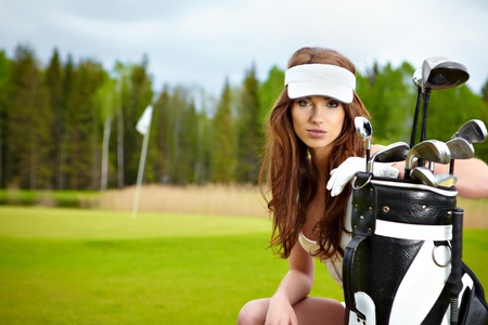 ponytail: Young brunette woman with golf equpment  Stock Photo